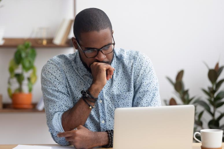 frustrated black man looking at computer screen