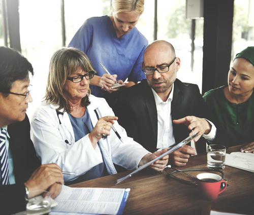 2 female doctors, two men and one woman sitting at a table taking notes and looking at an ipad