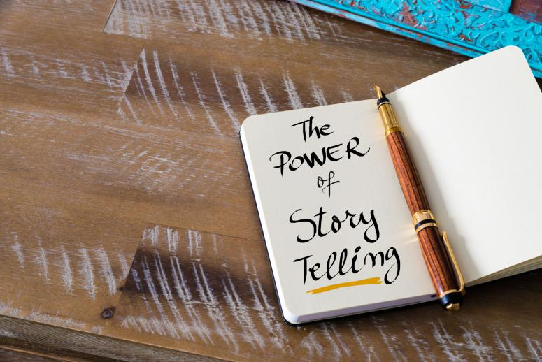 Retro effect and toned image of notebook next to a fountain pen. Business concept image with handwritten text THE POWER OF STORY TELLING